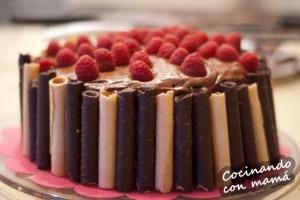 Tarta de chocolate de tres pisos con frambuesas, buttercream de chocolate y barquillos